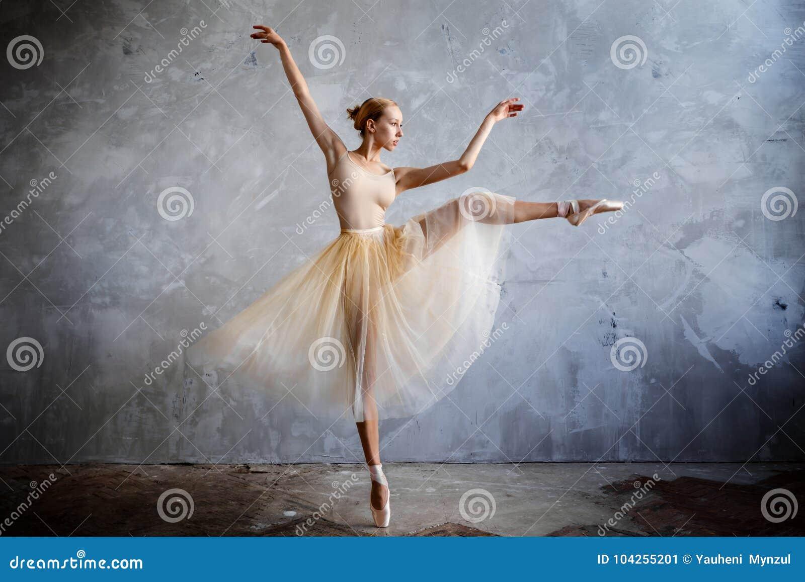 Młoda balerina w złotym barwionym dancingowym kostiumu pozuje w loft studiu