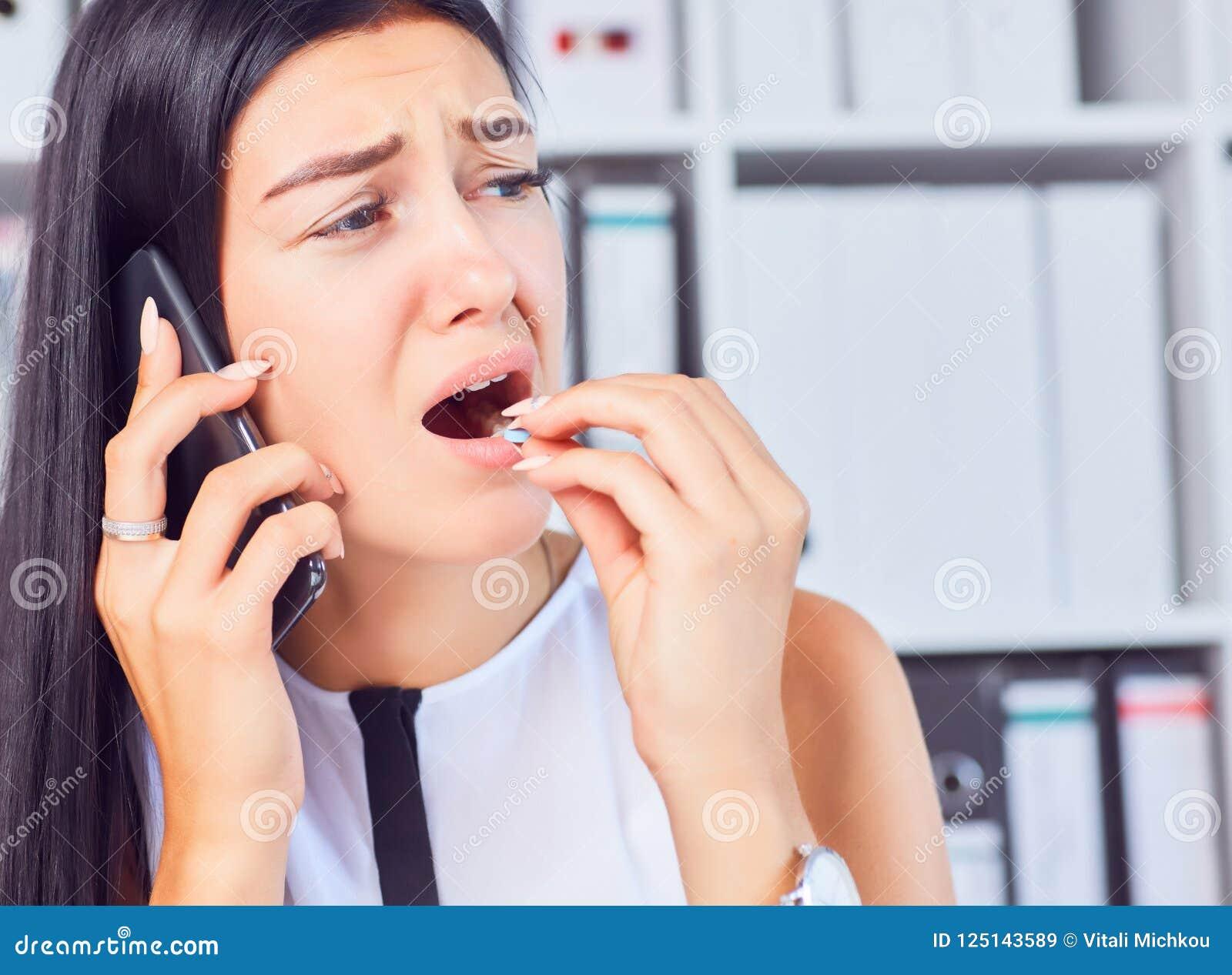 Młoda biznesowa kobieta bierze medycynę w stresującej sytuaci przy miejscem pracy Kobieta konsultuje na telefonie z jej lekarką