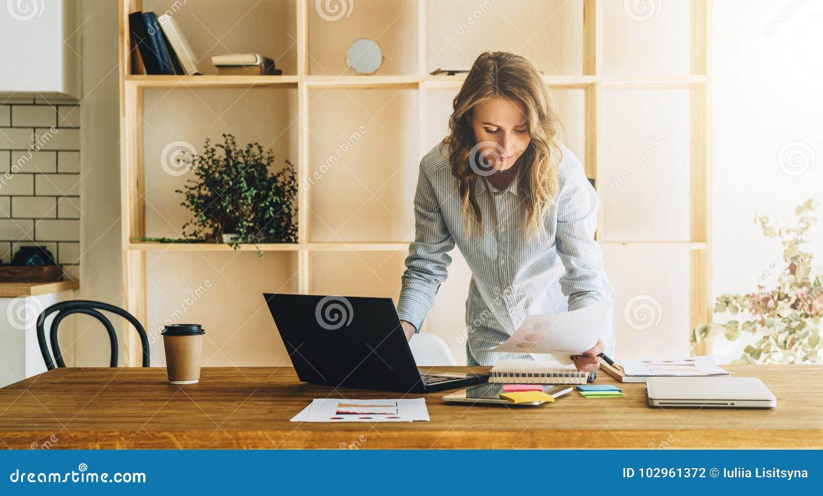 Młoda bizneswoman kobieta stoi blisko kuchennego stołu, czyta dokumenty, uses laptop, działanie, studiowanie