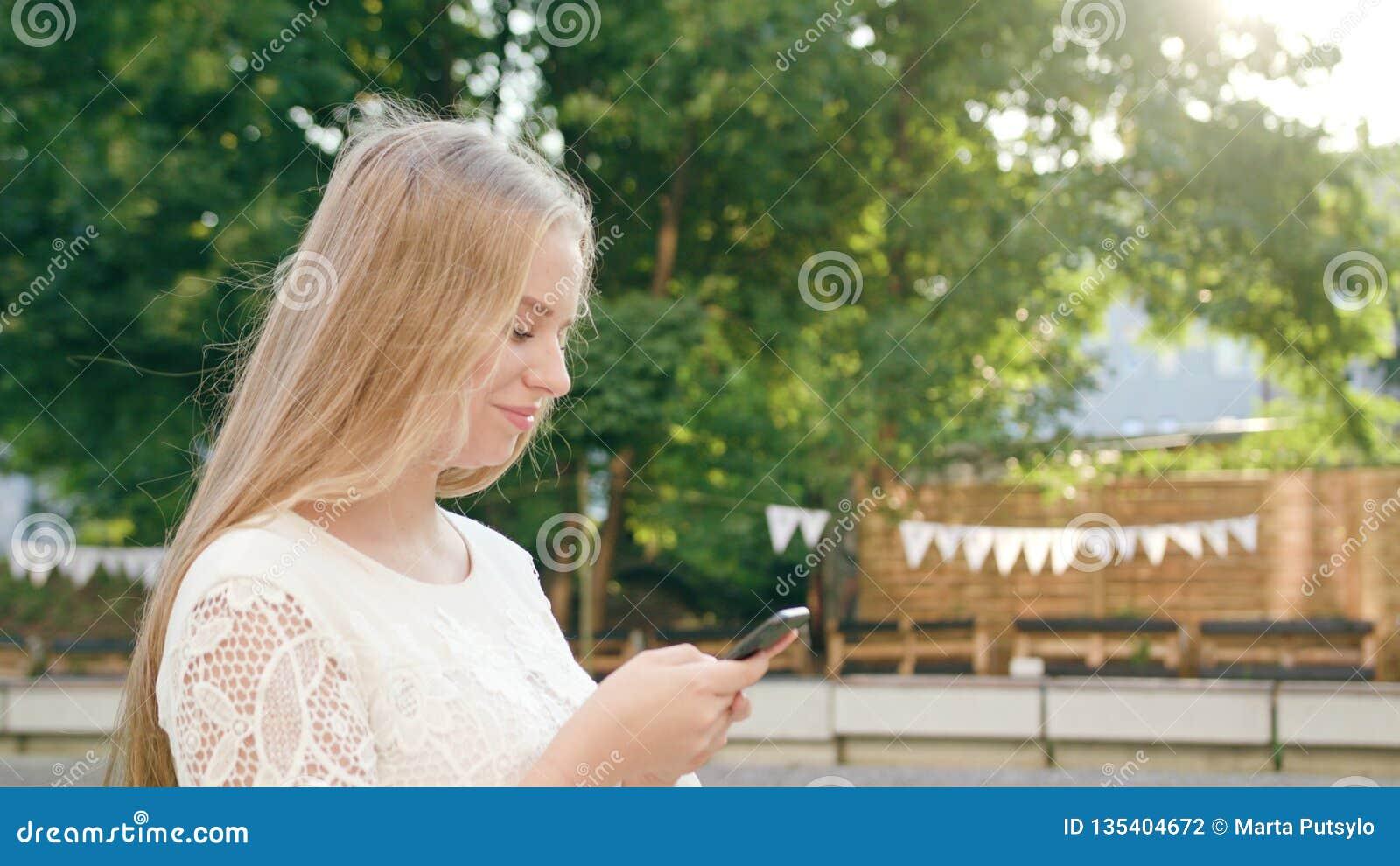 Młoda blondynki dama Chodzi telefon i Używa w miasteczku