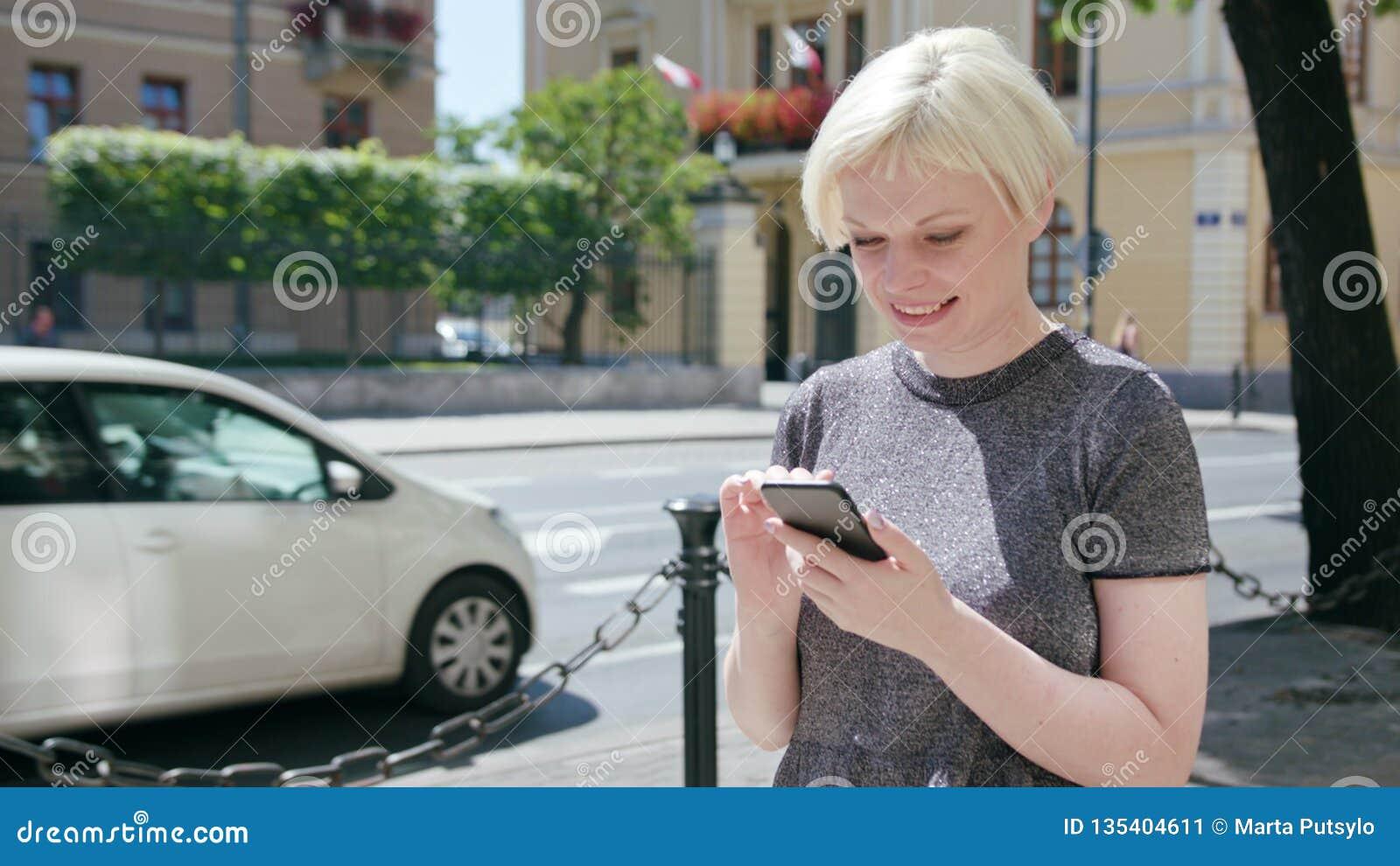 Młoda blondynki dama Używa telefon w miasteczku