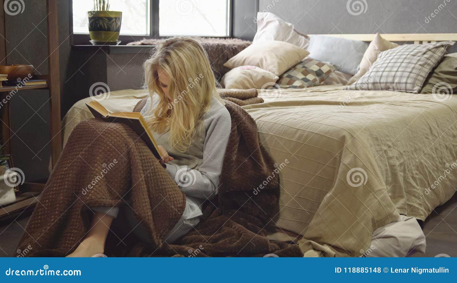 Młoda blondynki dziewczyna siedzi na podłoga w koc obok łóżka i czyta książkę