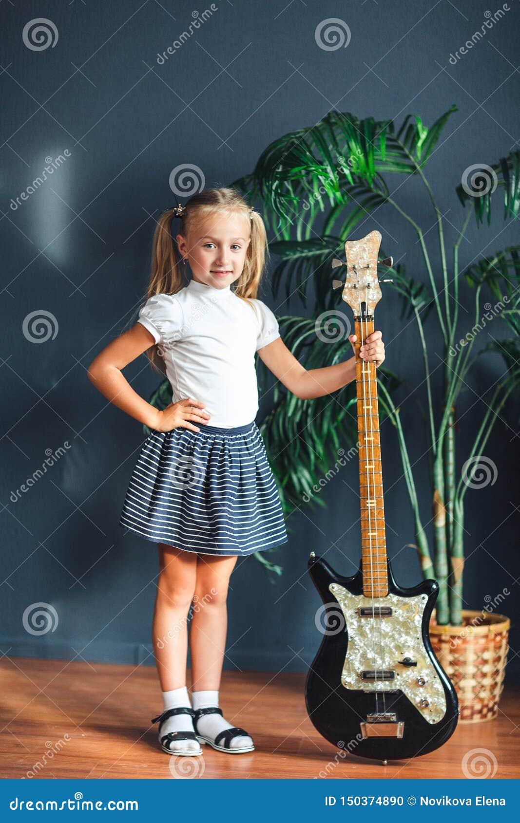 Młoda blondynki dziewczyna z ogonami w koszulce, spódnicie i sandałach z gitarą elektryczną białych, w domu patrzeje kamerę i uśm