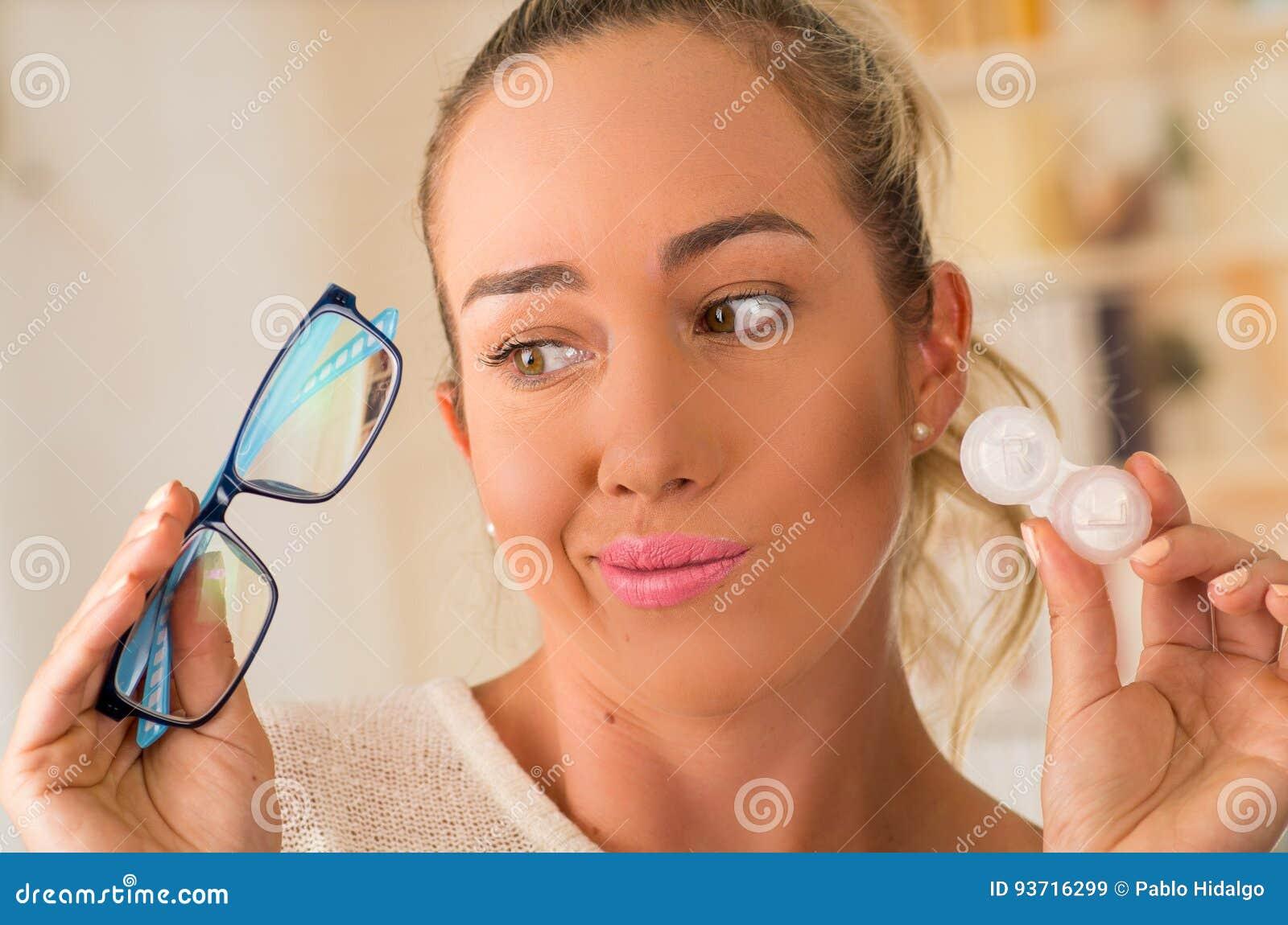 Młoda blondynki kobiety mienia szkła kontaktowe skrzynka na ręce i mienie w jej inny wręczamy błękitnych szkła na zamazanym tle