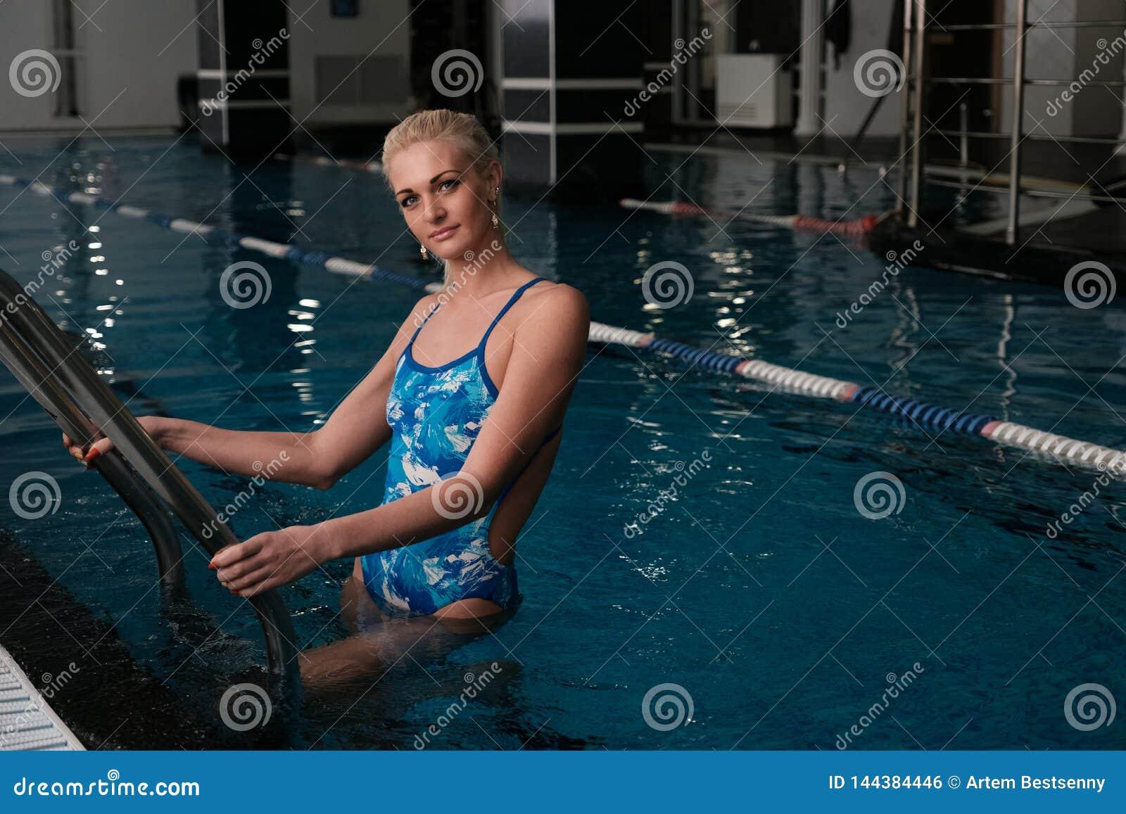Młoda blondynki kobiety pozycja w zamkniętym mieniu i basenie poręcze schodki, patrzeje kamerę