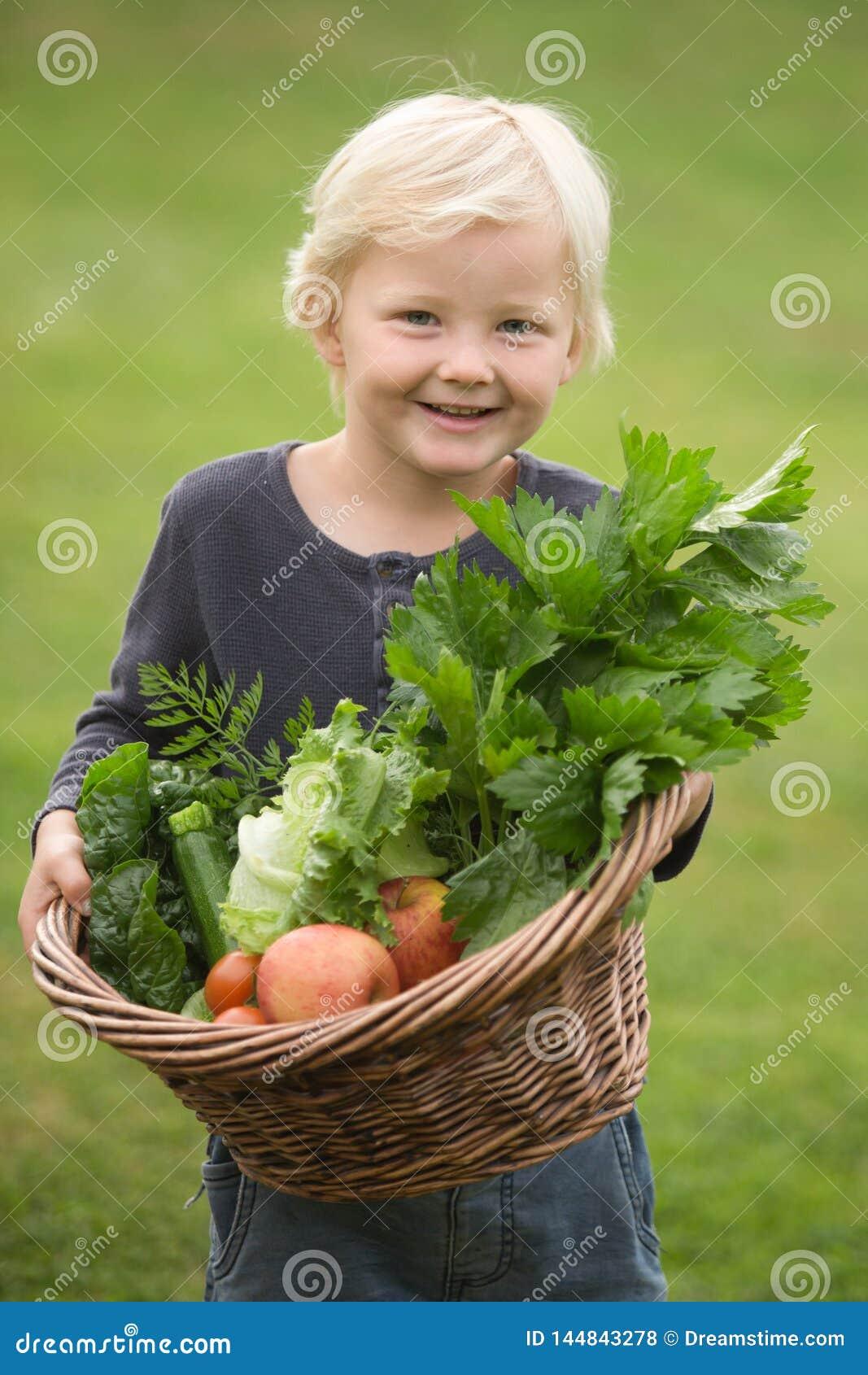 Młoda blondynki ogrodniczka dumnie pokazuje daleko jego żniwo