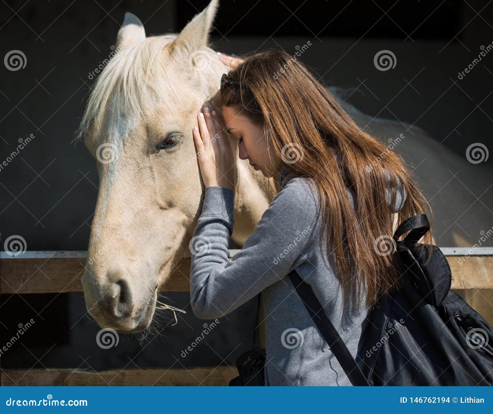 Młoda brunetka zaprzyjaź się konia