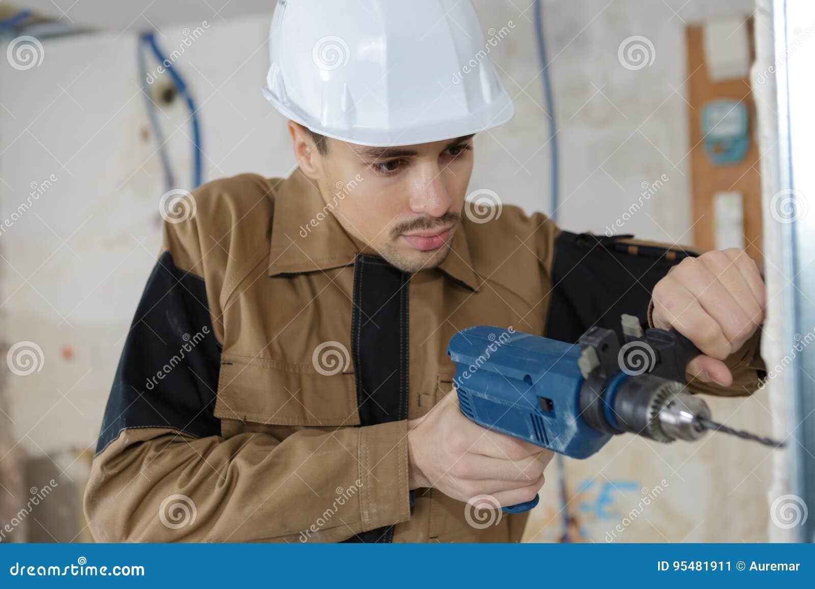 Młoda buider musztrowania ściana z świderu perforatorem