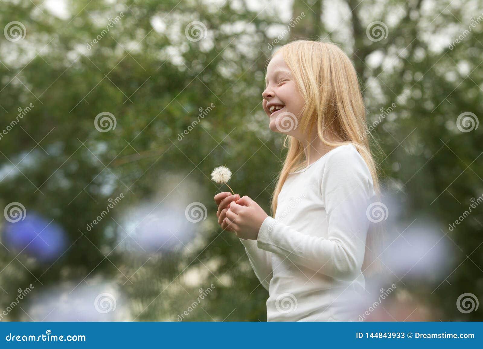 Młoda caucasian dziewczyna życzy na dandelion