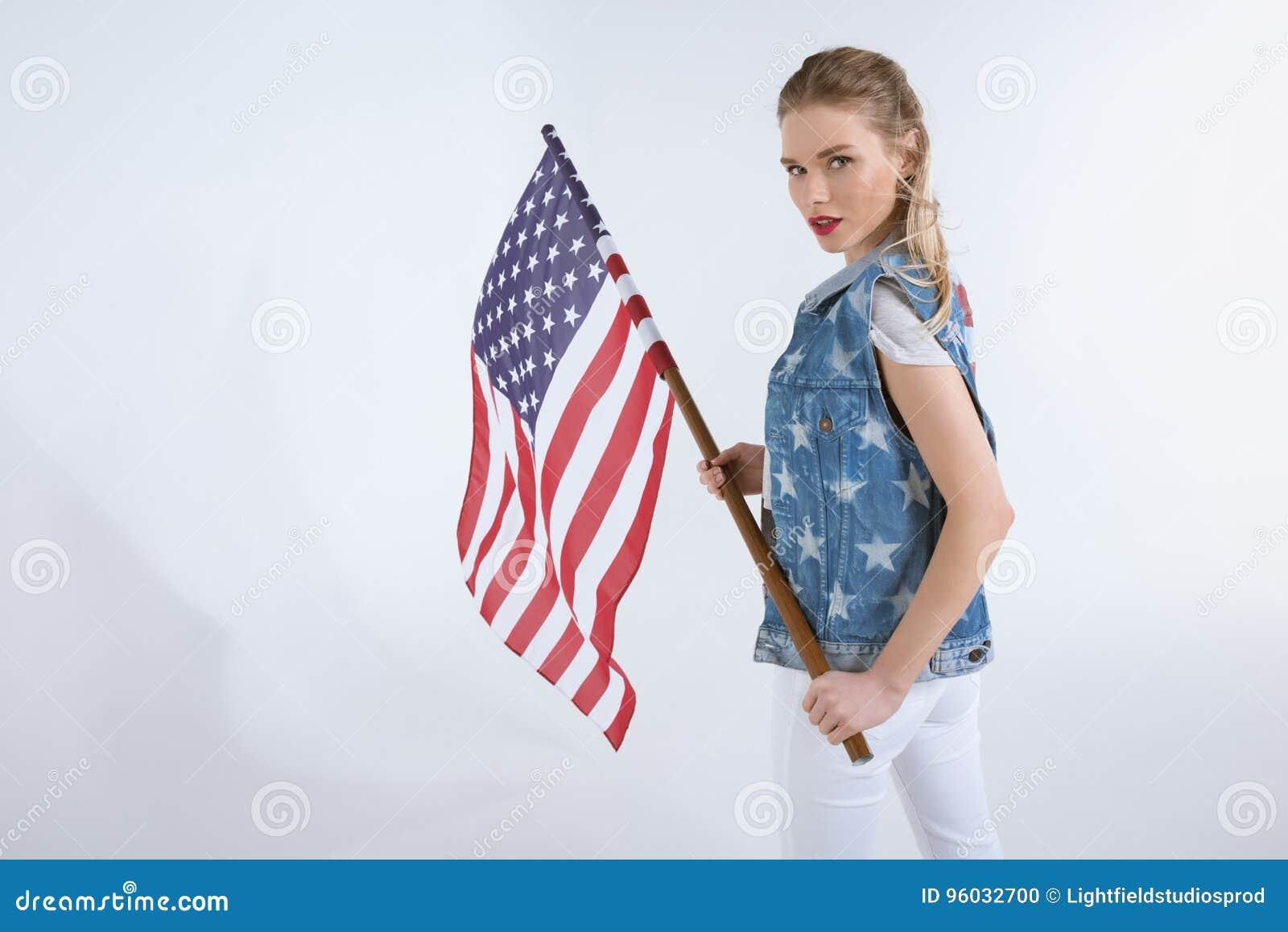 Młoda caucasian dziewczyna patrzeje kamerę i macha usa flaga