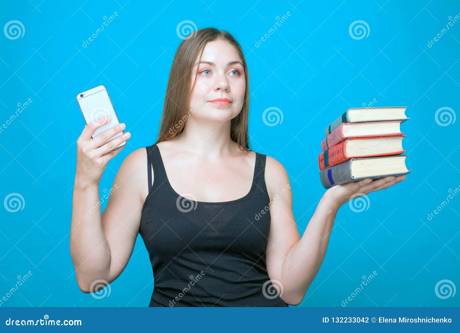 Młoda caucasian kobieta z książki i telefon komórkowy