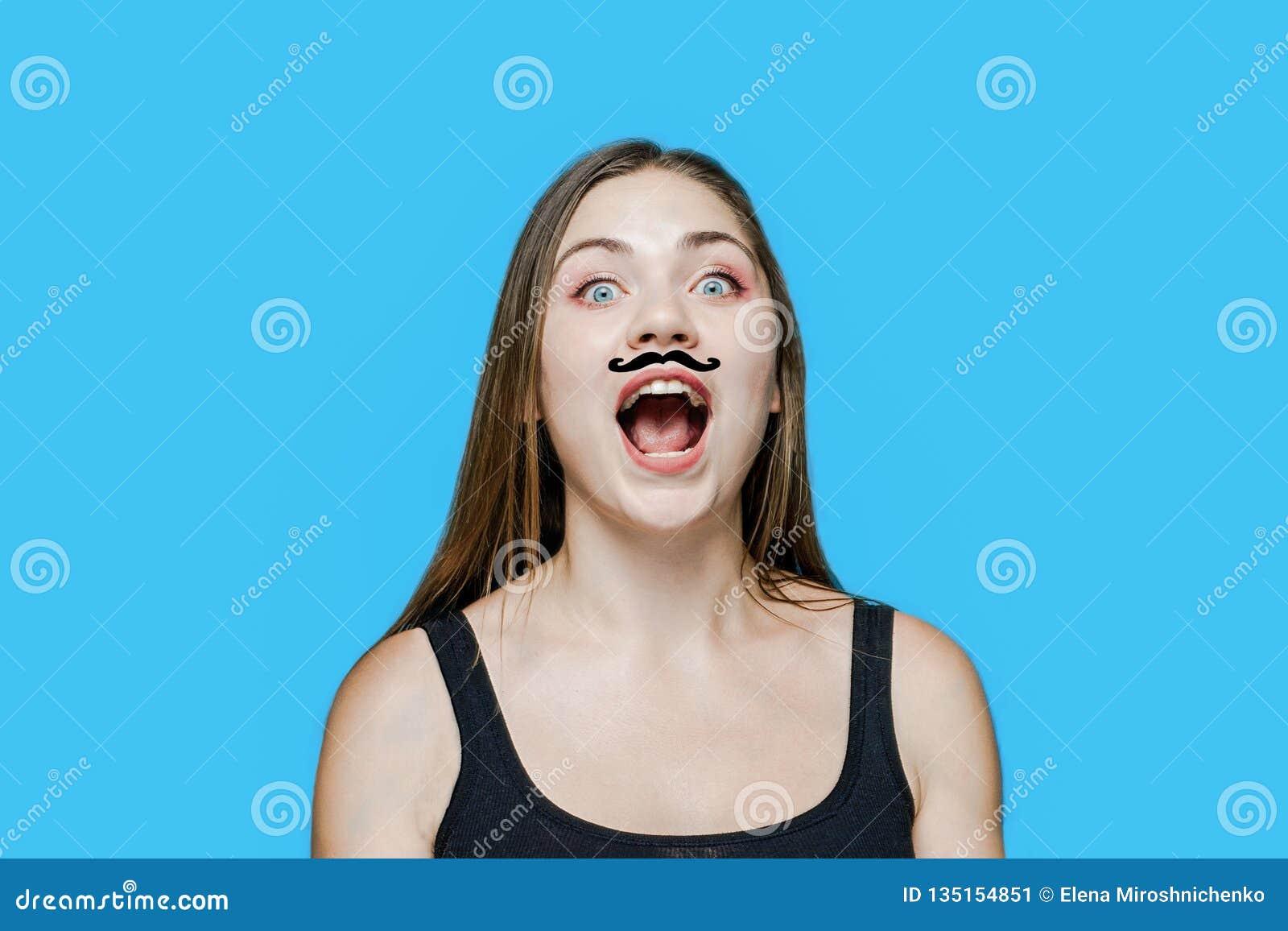 Młoda caucasian kobieta z patroszonym wąsem na jej twarzy krzyczy, otwierający usta