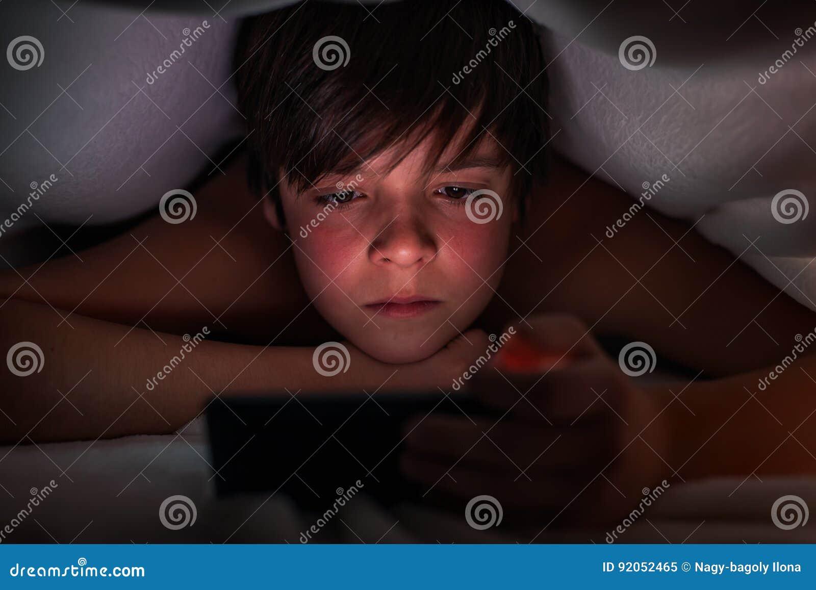 Młoda chłopiec chuje pod koc i ogląda jego telefon