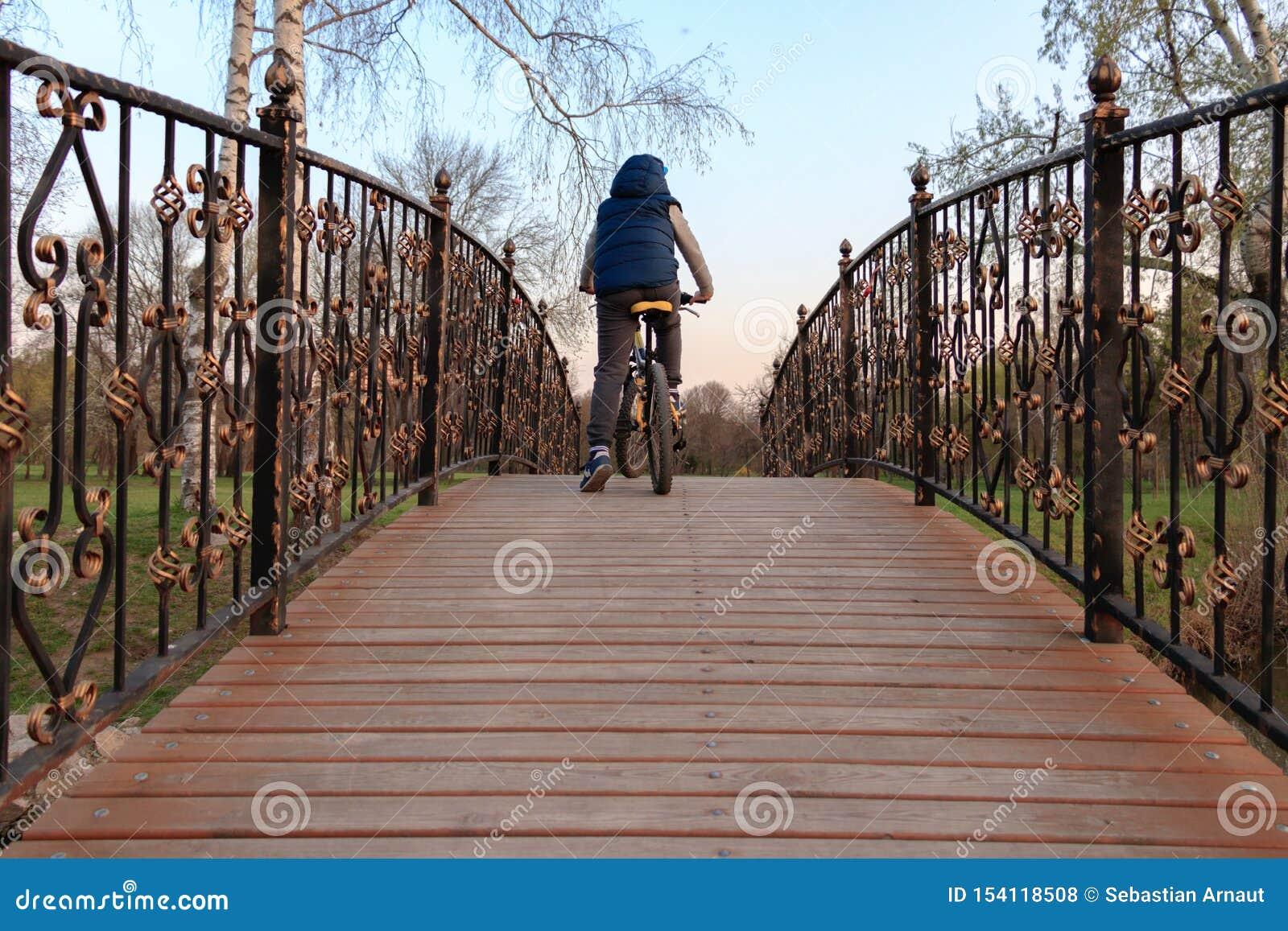 Młoda chłopiec jedzie bicykl nad drewnianym mostem