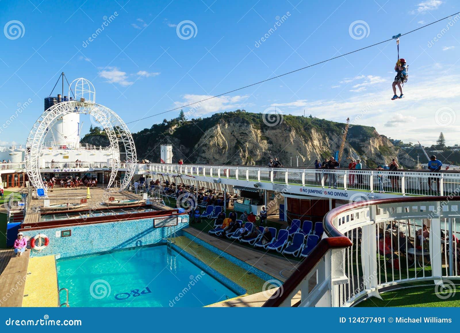 Młoda chłopiec jedzie zamek błyskawiczny linii wysokość nad basenu pokład rejsu liniowiec