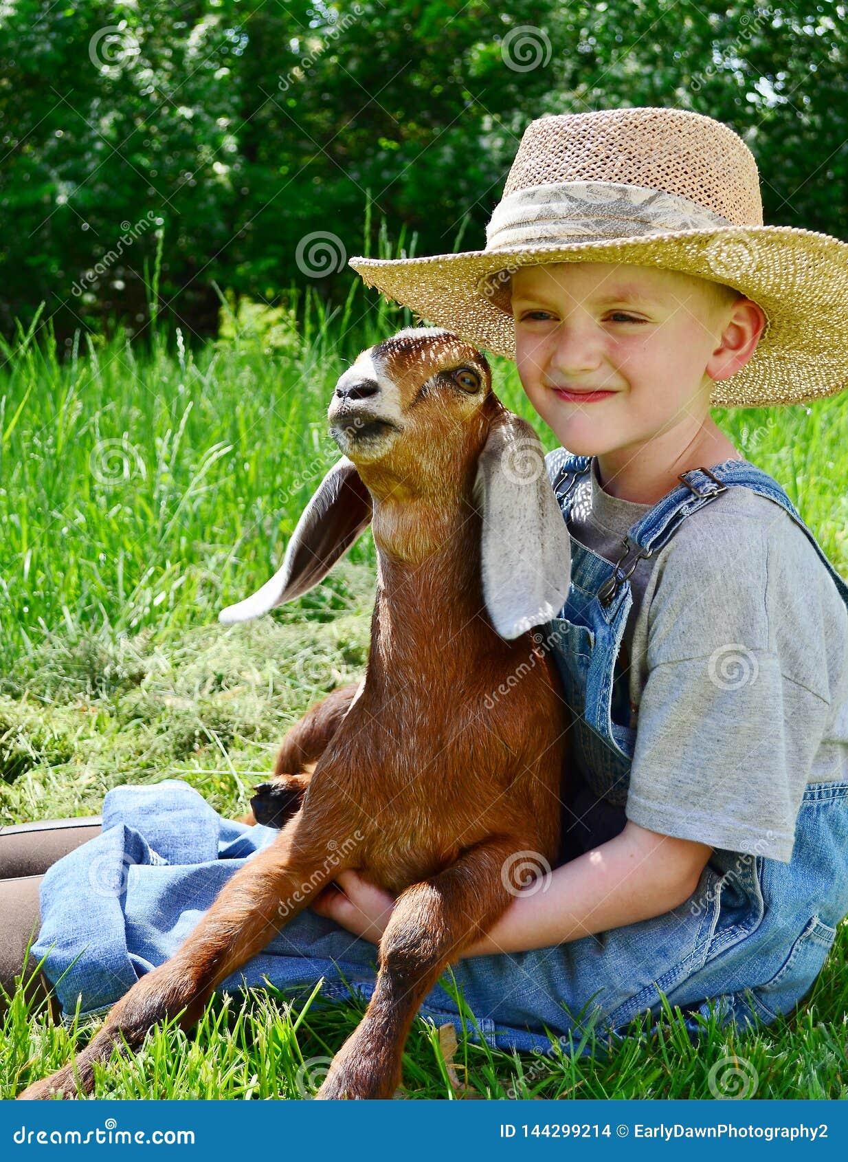 Młoda chłopiec mienia dziecka kózka