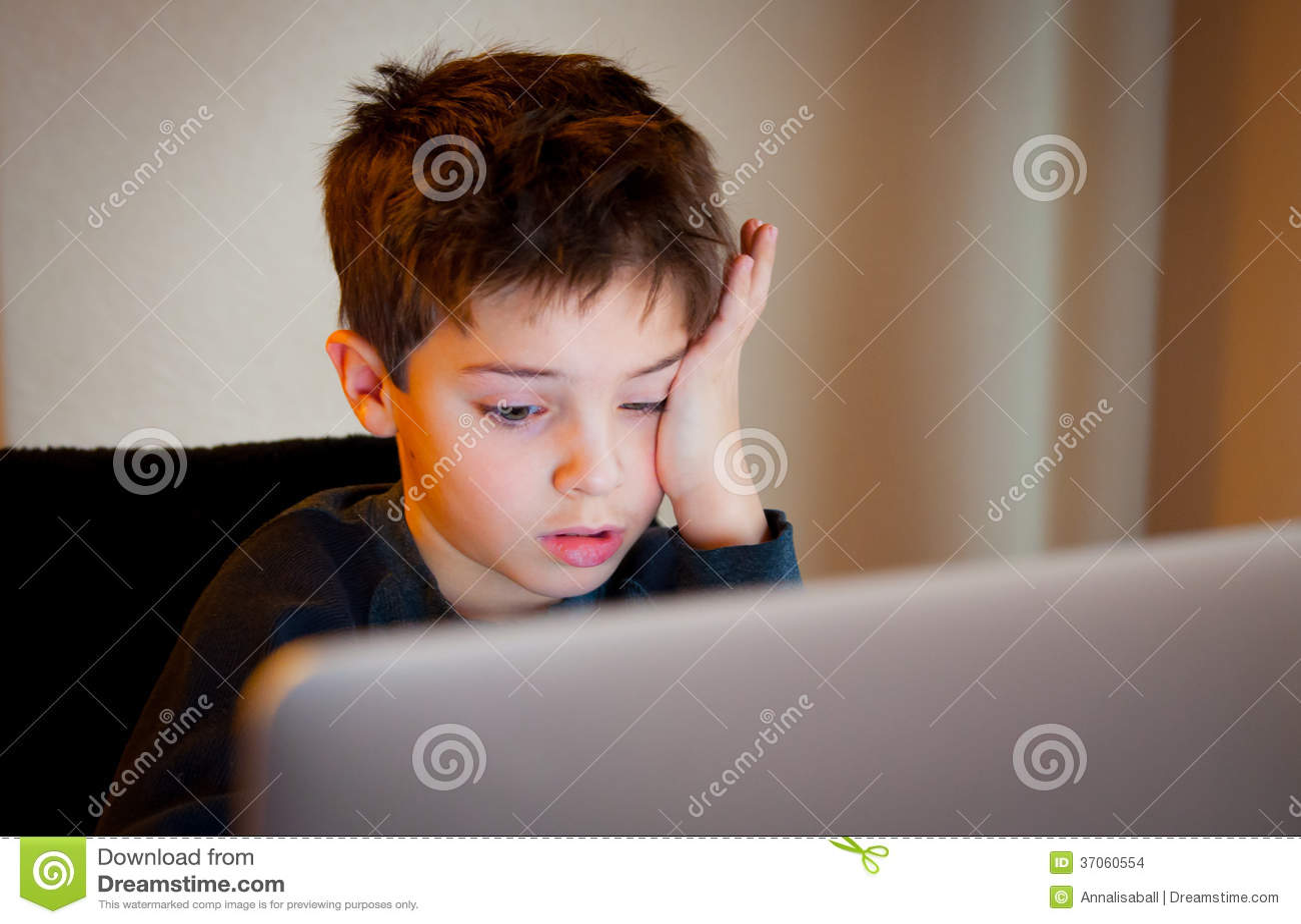 Młoda chłopiec patrzeje ekran komputerowego