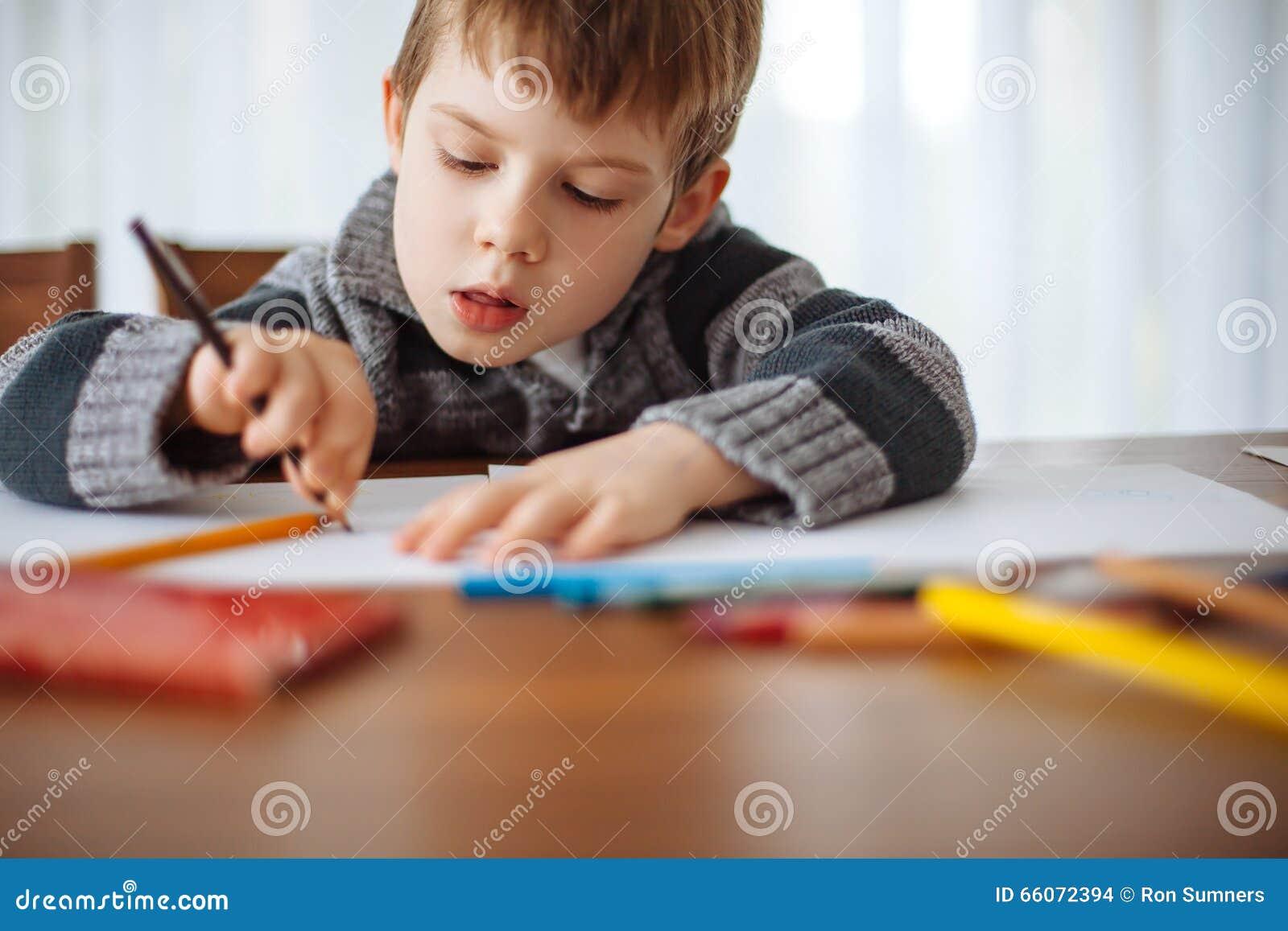 Młoda chłopiec rysuje w domu