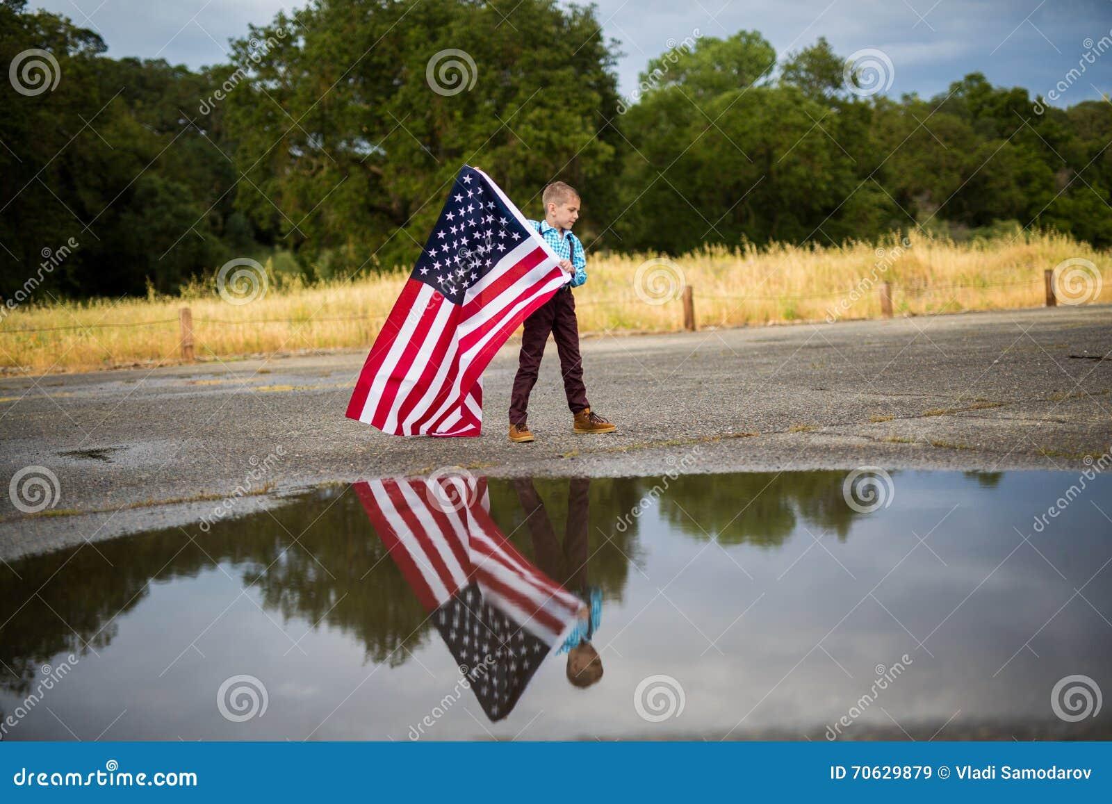 Młoda chłopiec trzyma wielką flaga amerykańską pokazuje patriotyzm dla jego swój kraju, Jednoczy stany