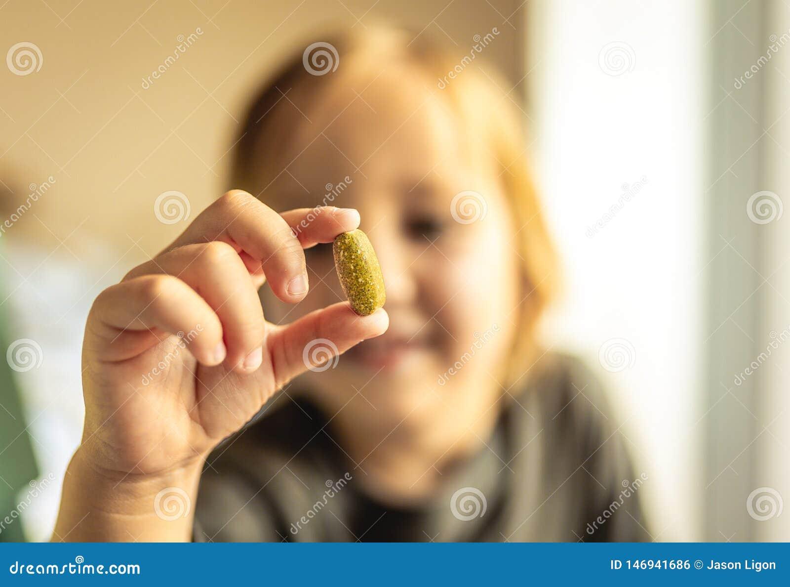 Młoda chłopiec trzyma witaminy lub recepty pigułkę z palcami przed twarzą t?o zamazywa? opieki poj?cia twarzy zdrowie maski pigu?