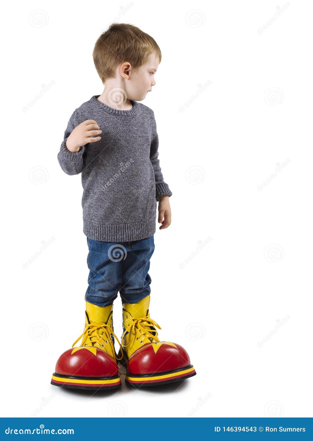 Młoda chłopiec z dużymi błazenów butami