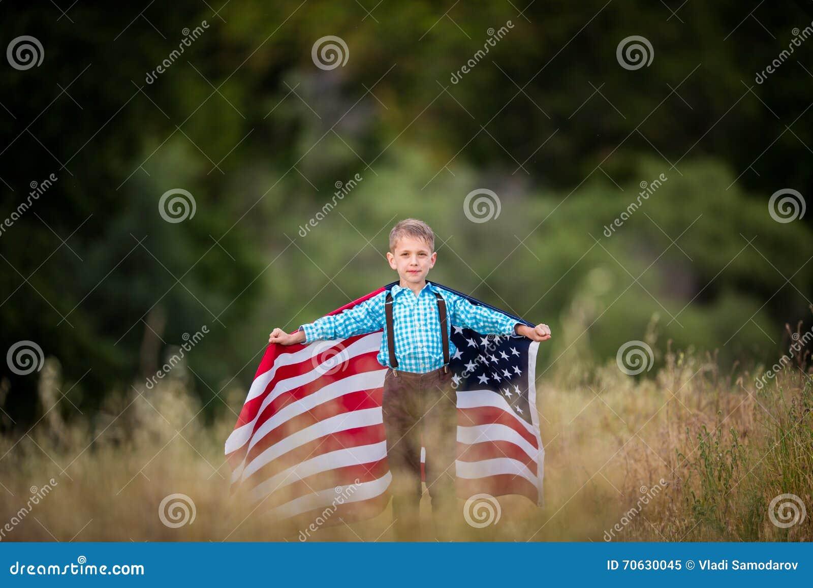 Młoda chłopiec z wielką flaga amerykańską pokazuje patriotyzm dla jego swój kraju, Jednoczy stany