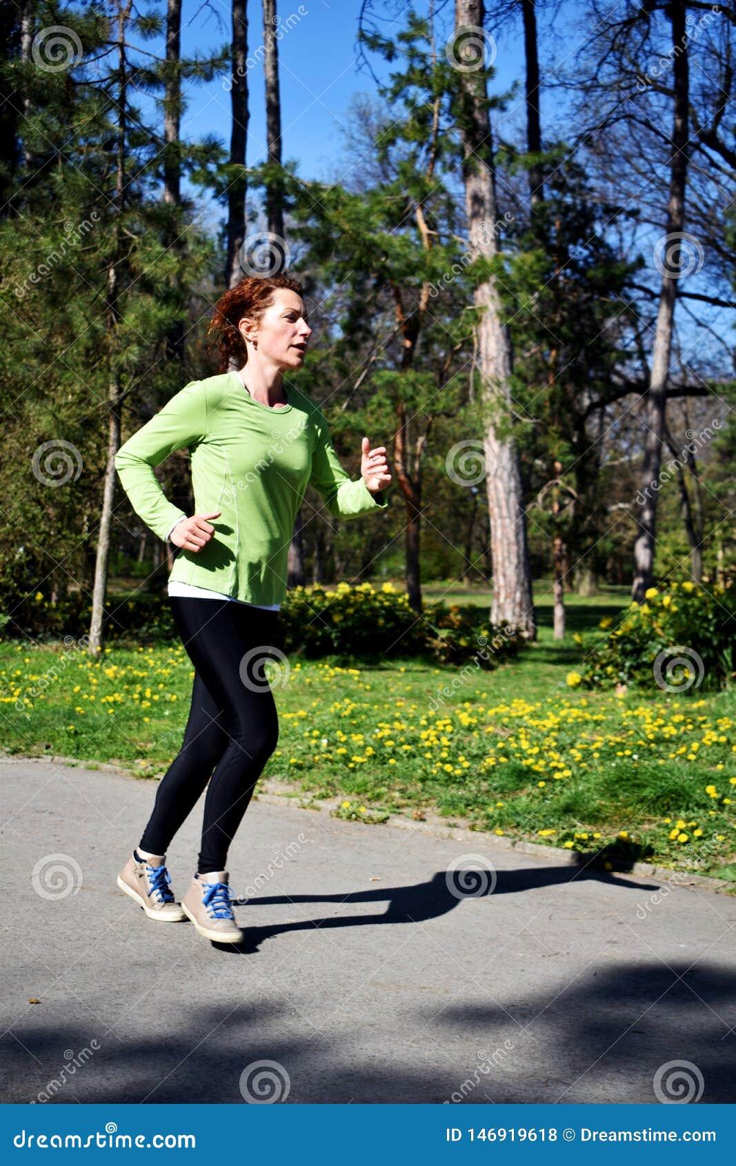 Młoda czerwona włosiana dama w zielonej koszula robi ona biega szkolenie w parku 1