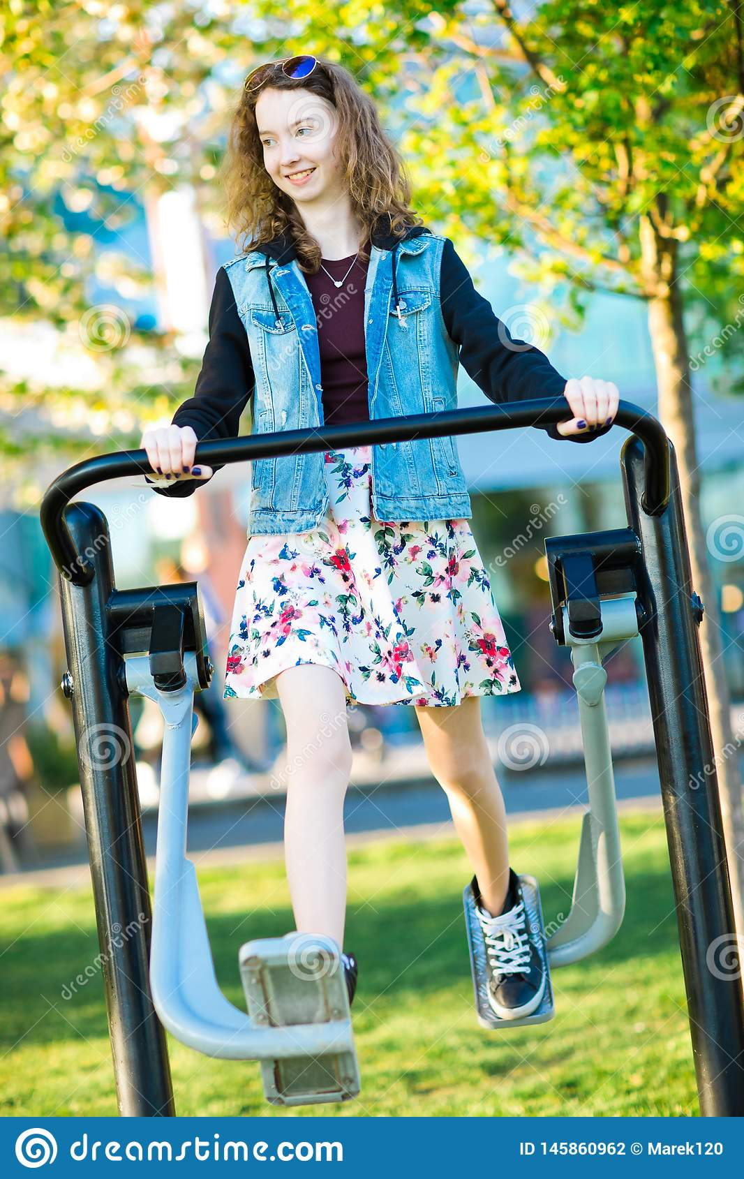 Młoda dziewczyna biega gym maszynę plenerową ubierał w spódnicowym ćwiczeniu