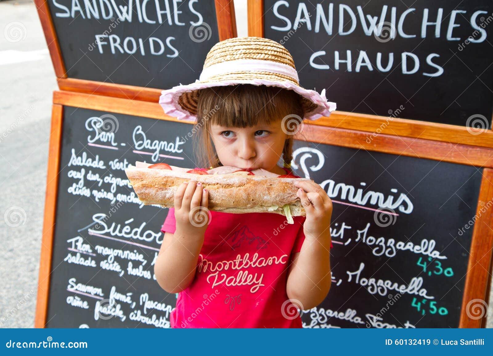 Młoda dziewczyna je dużą kanapkę