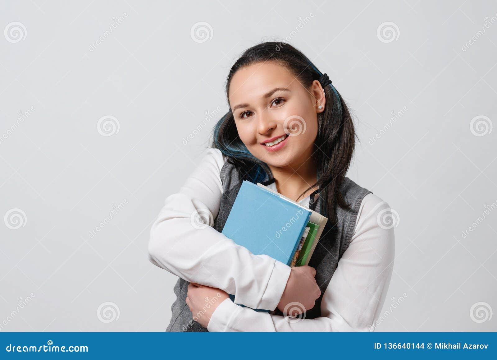 Młoda dziewczyna jest uczniem szkoła średnia uczeń z stertą podręczniki w jej rękach Na białym tle