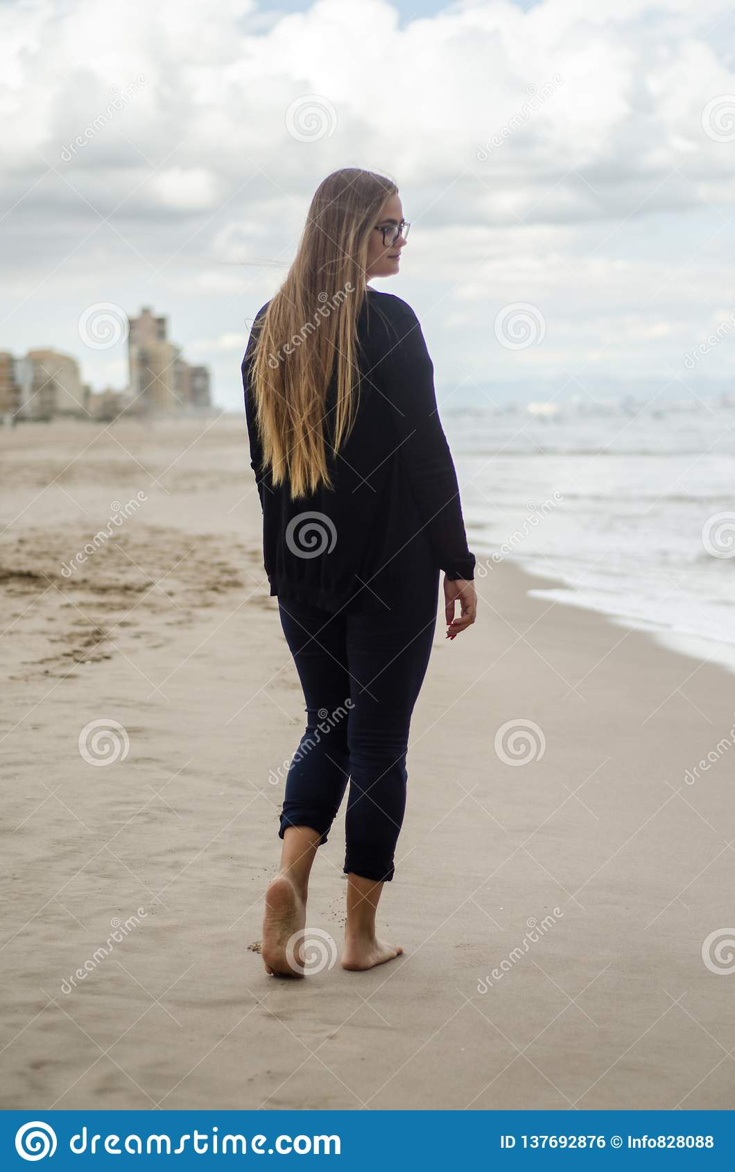 Młoda dziewczyna na jego z powrotem, chodzący na plaży na chmurnym dniu