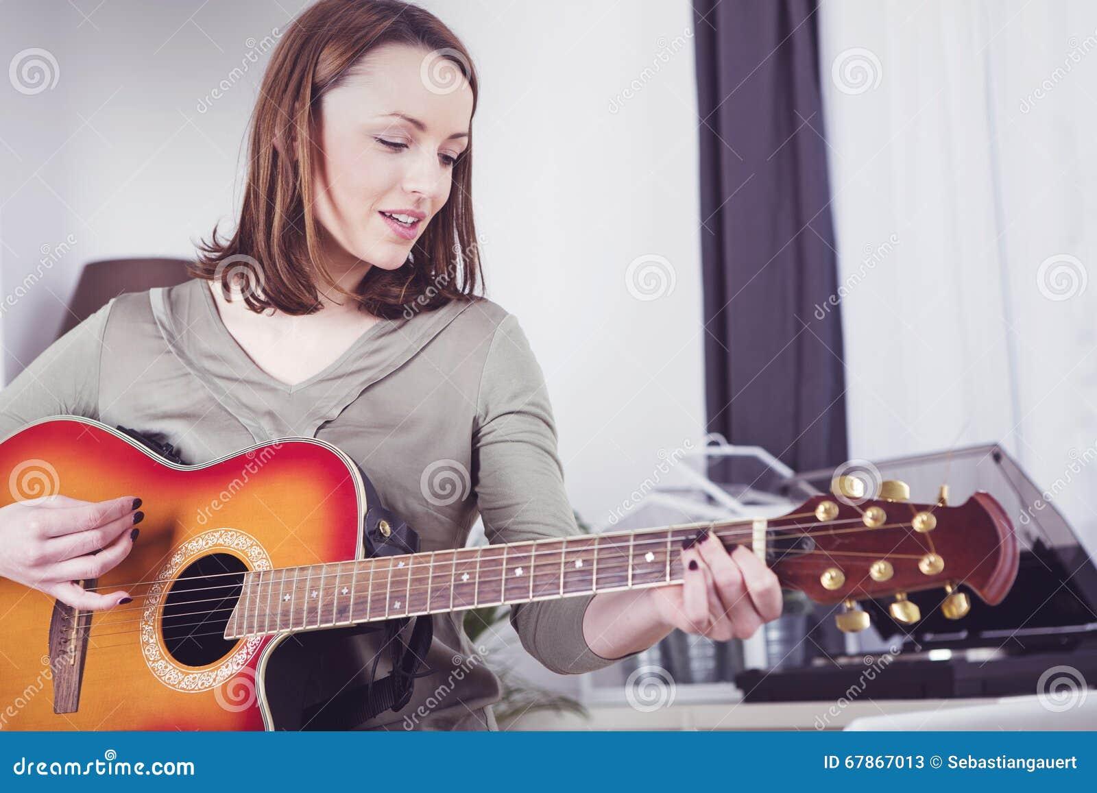 Młoda dziewczyna na kanapie bawić się gitarę