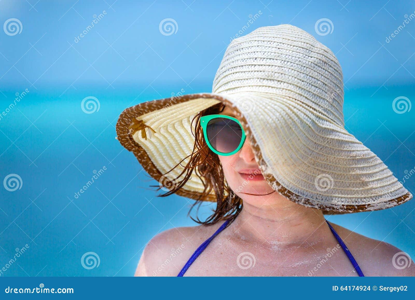 Młoda dziewczyna na plaży w zielonych szkłach