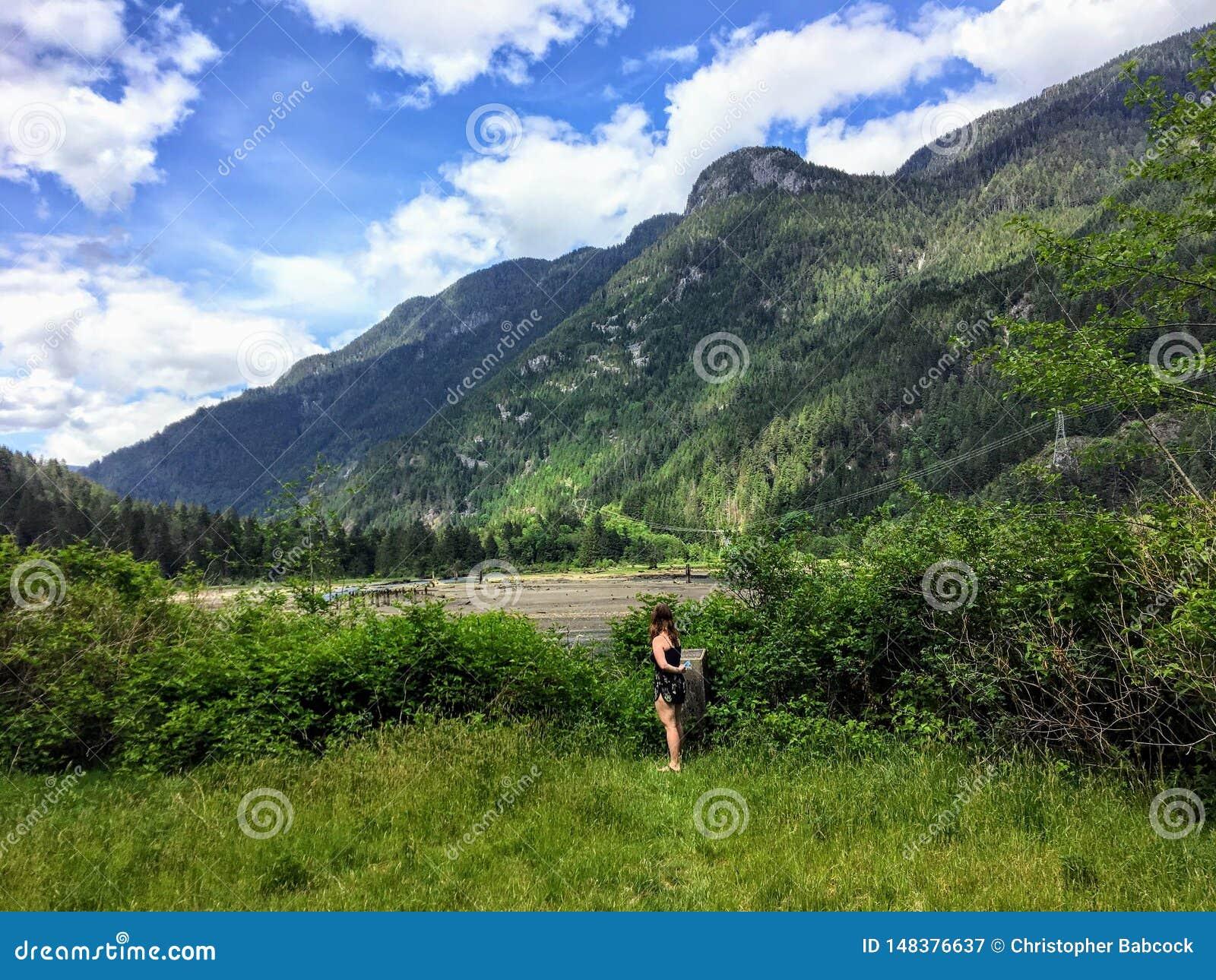 Młoda dziewczyna podziwia niewygładzonego pilota krajobraz w odległości wliczając piaska przy punktem obserwacyjnym, deponuje pie