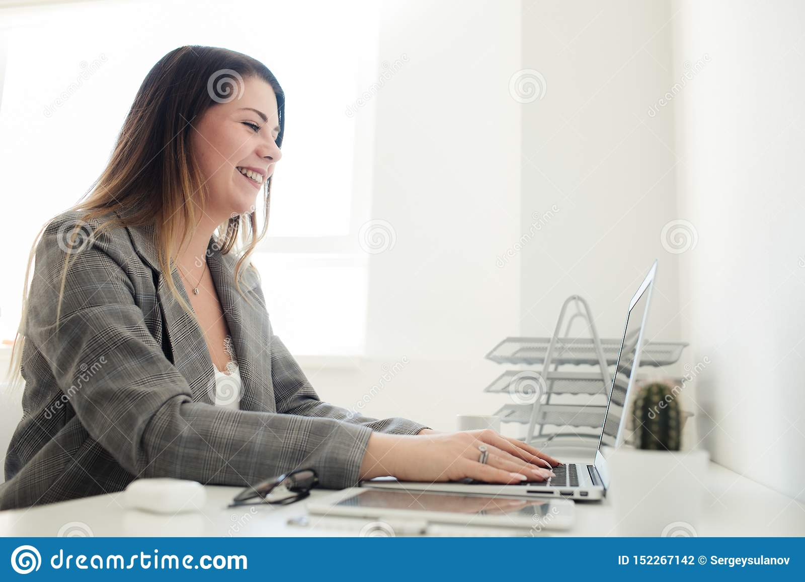 Młoda dziewczyna pracuje w biurze przy stołem