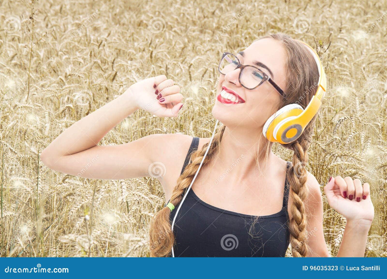 Młoda dziewczyna słucha muzyka i taniec w pszenicznym polu