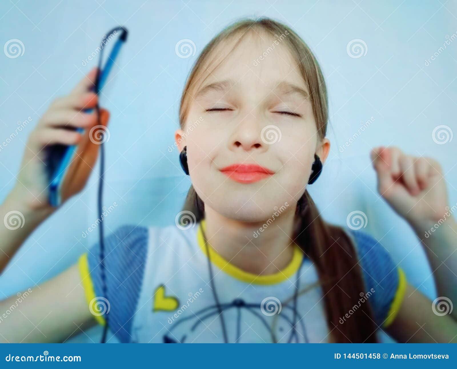 Młoda dziewczyna słucha muzyka przez telefonu