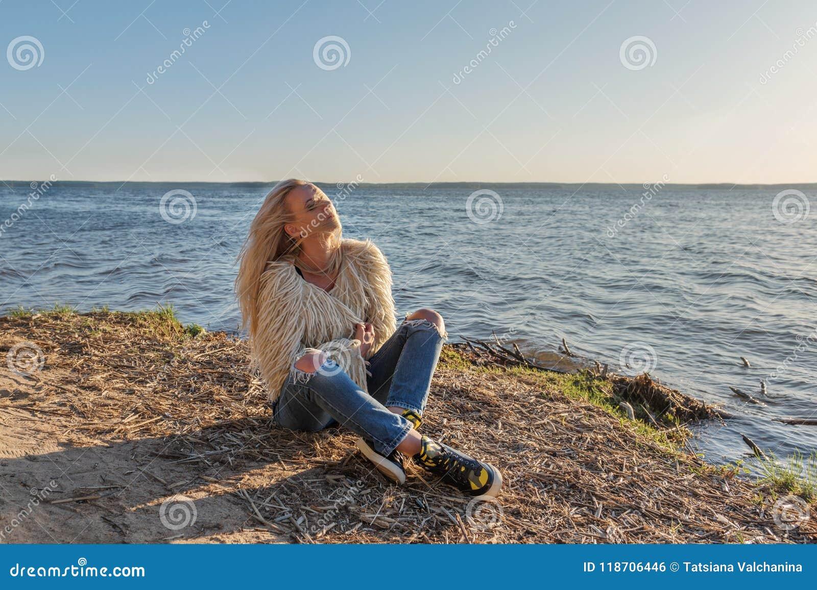 Młoda dziewczyna siedzi lounging na brzeg staw i wiatr dmucha jej blondyn