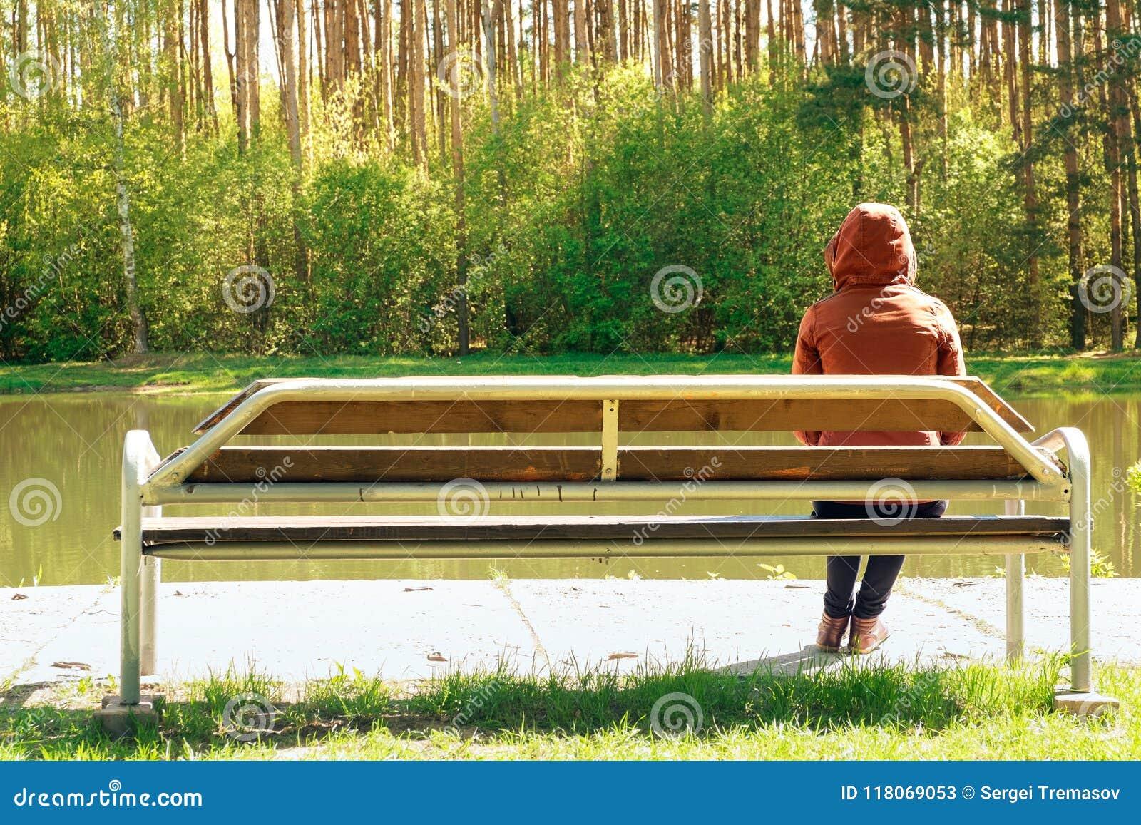 Młoda dziewczyna smutna i siedzi na drewnianej ławce w parku, ona rozczarowywał słodką miłością Sen przyszłość