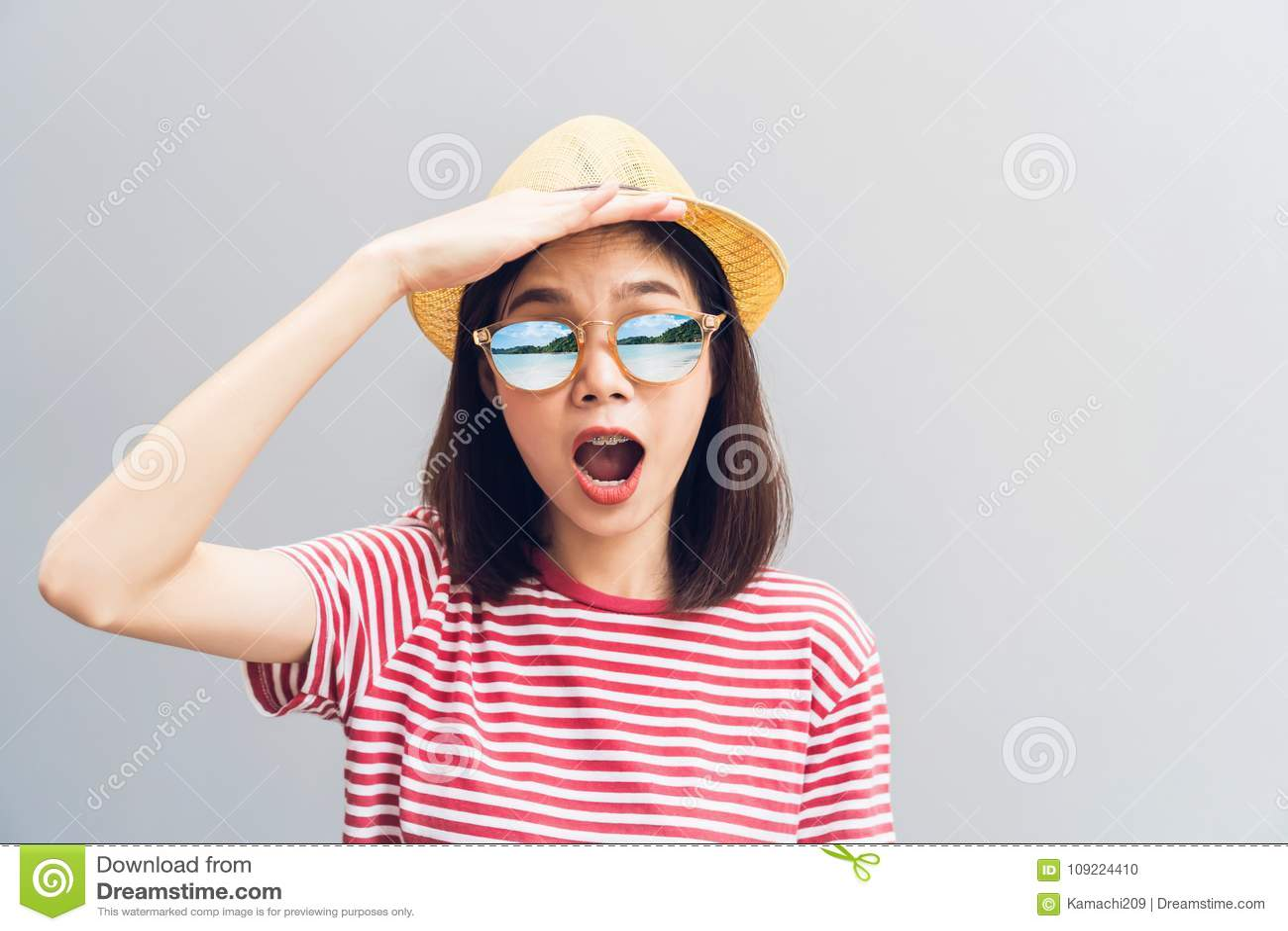 Młoda dziewczyna szczęśliwa jest Przyglądająca znajdować coś naprzód Jest ubranym okulary przeciwsłonecznych z odbiciem wyspa i p
