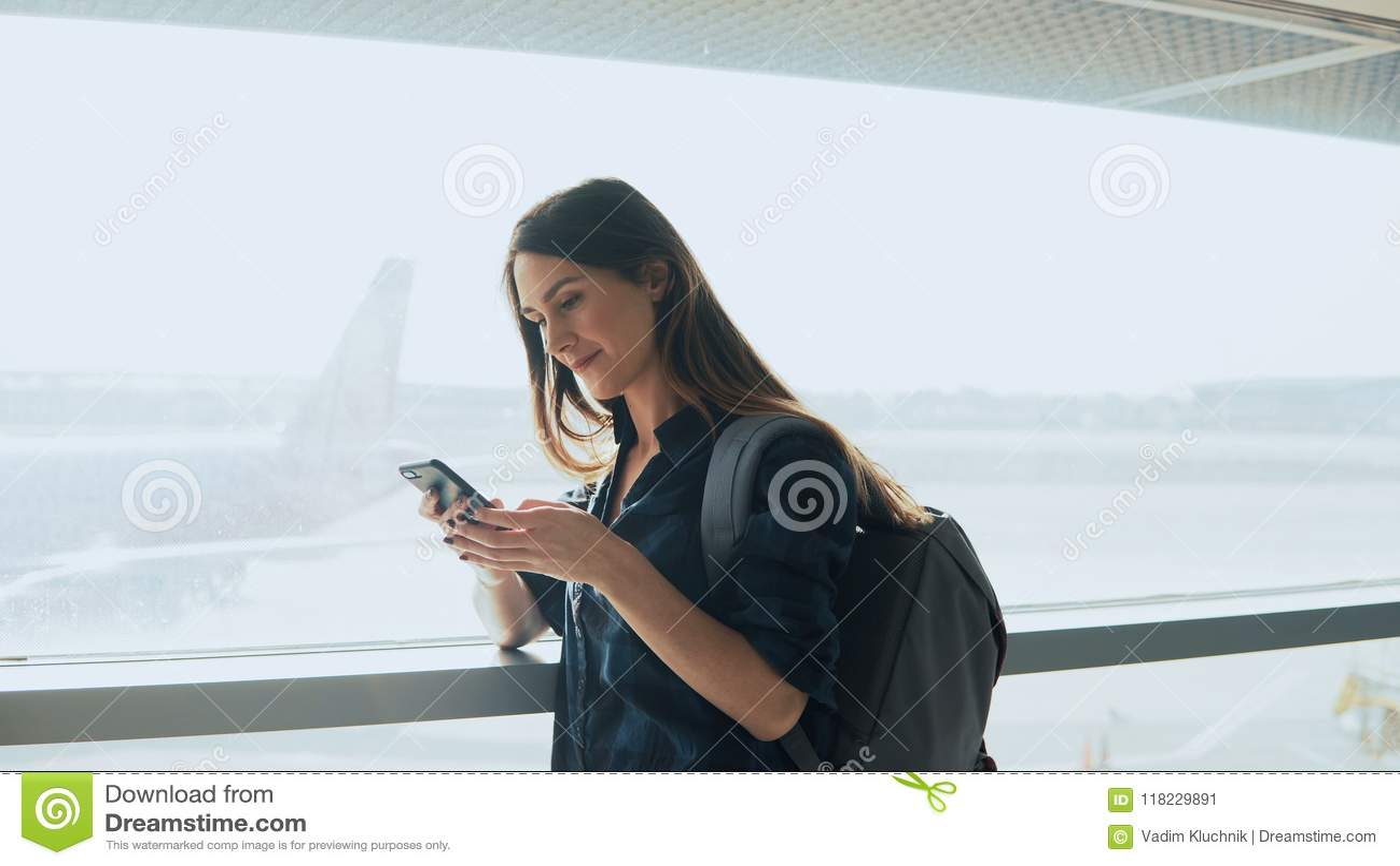 Młoda dziewczyna używa smartphone blisko lotniskowego okno Szczęśliwa Europejska kobieta z plecakiem używa wiszącą ozdobę app w t