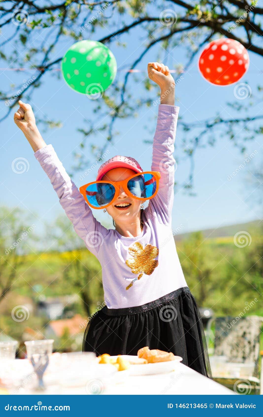 Młoda dziewczyna w śmiesznych dużych słońc szkłach na ogrodowym przyjęciu