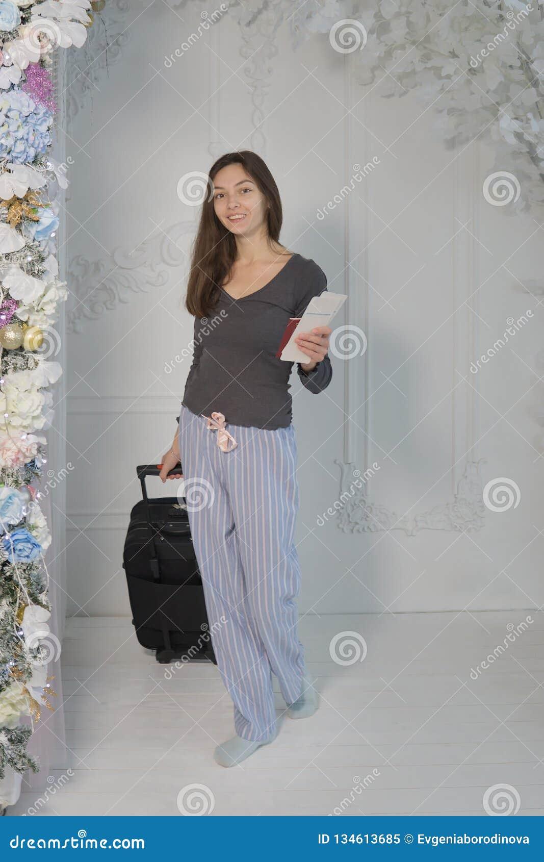 Młoda dziewczyna w brąz kurtce z biletami i paszport w jej ręk spojrzeniach przy kamerą, uśmiechamy się, niesiemy, walizkę