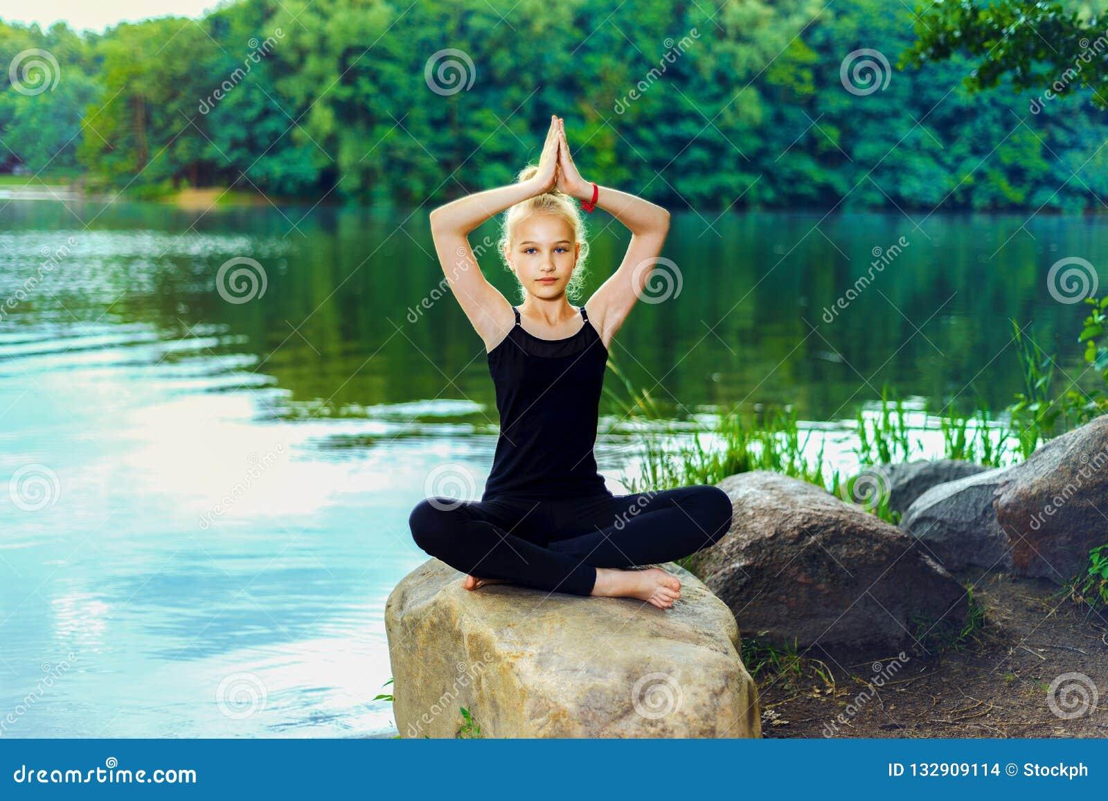 Młoda dziewczyna w czarnych leggings i koszulce siedzi na kamieniu w lotosowej pozie blisko jeziora