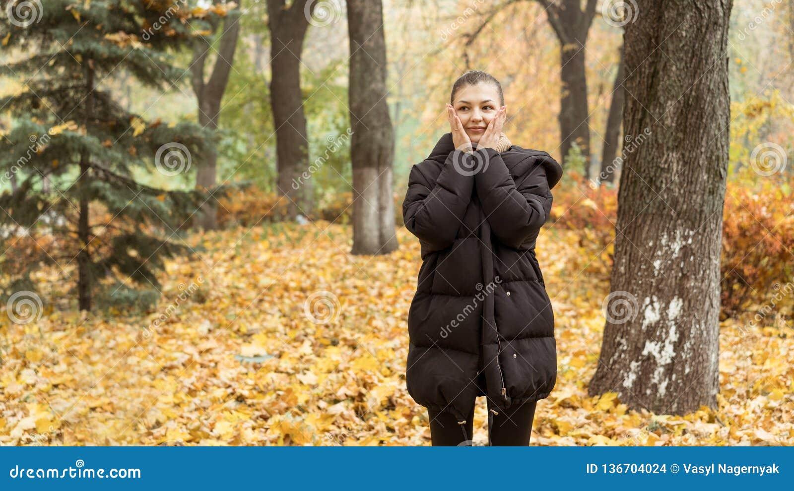 Młoda dziewczyna w jesień parku w czarnej kurtce