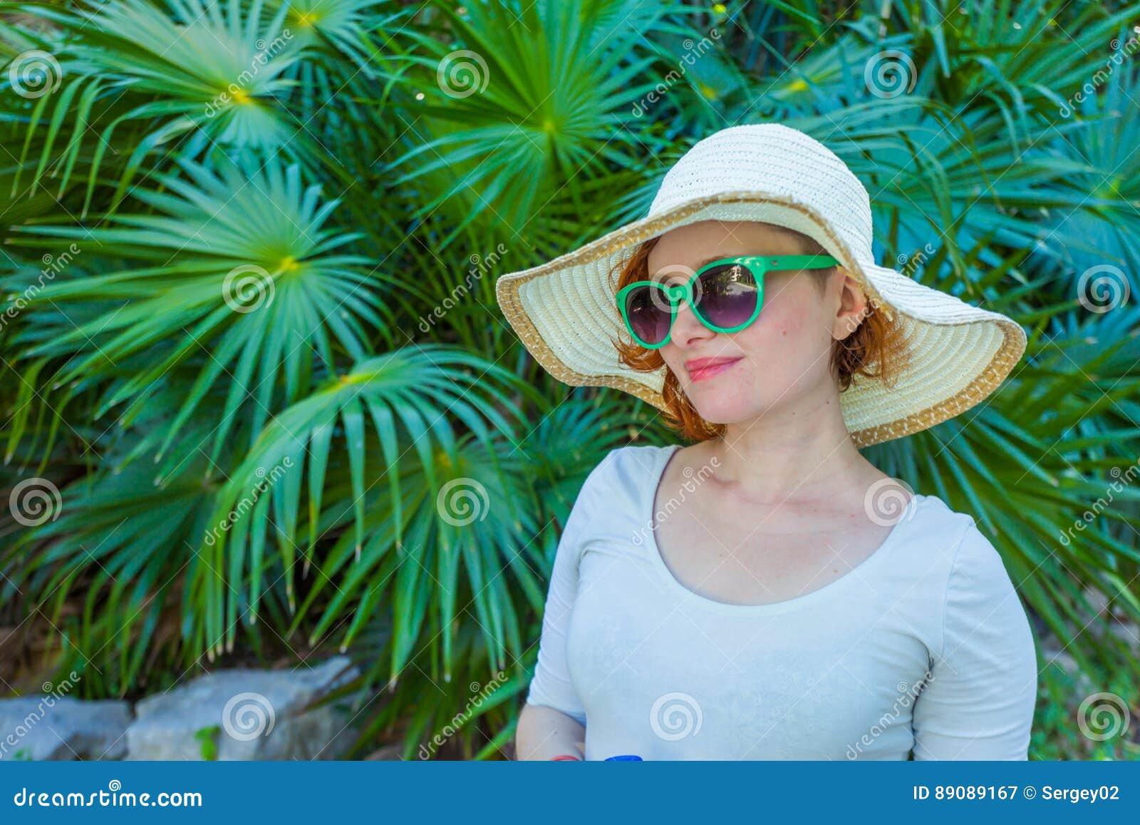 Młoda dziewczyna w parku w zielonych szkłach
