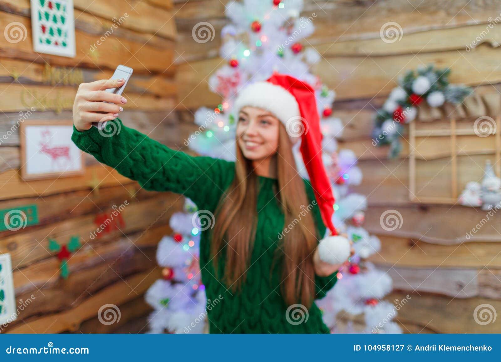 Młoda dziewczyna w Santa kapeluszu robi selfie na tle choinka