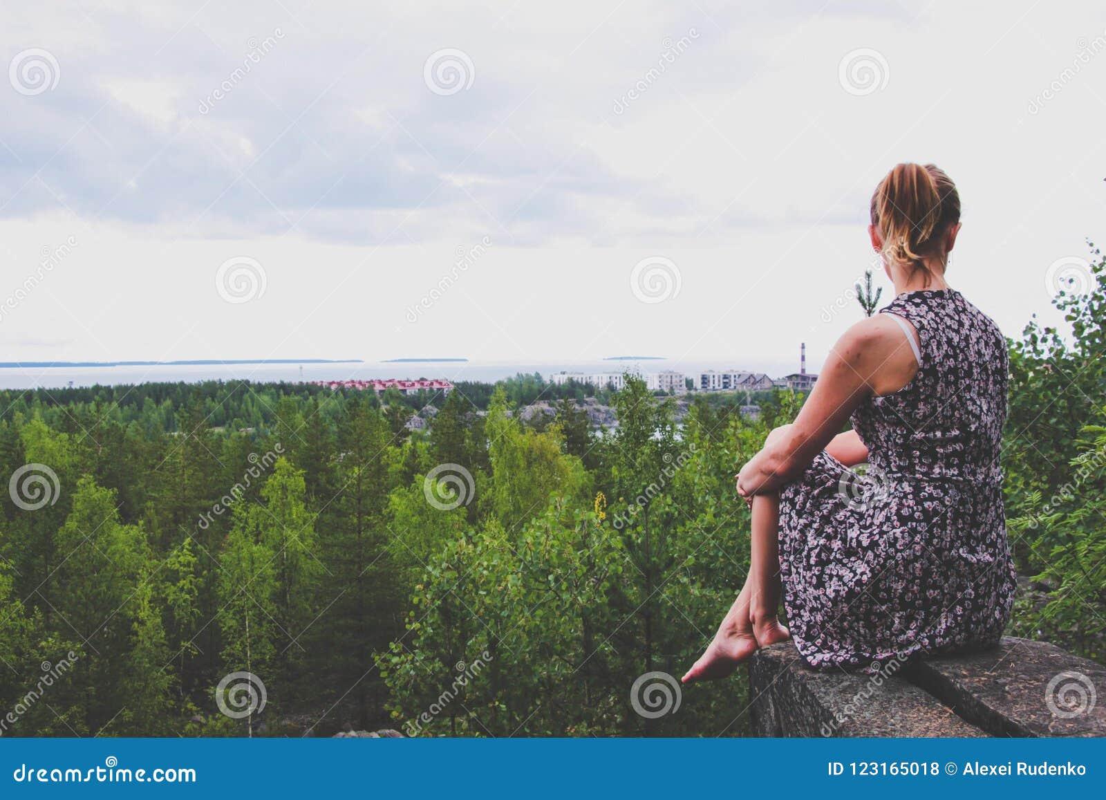 Młoda dziewczyna w sukni siedzi na rockowym wypuscie nad las który lokalizuje na brzeg ogromny jezioro,