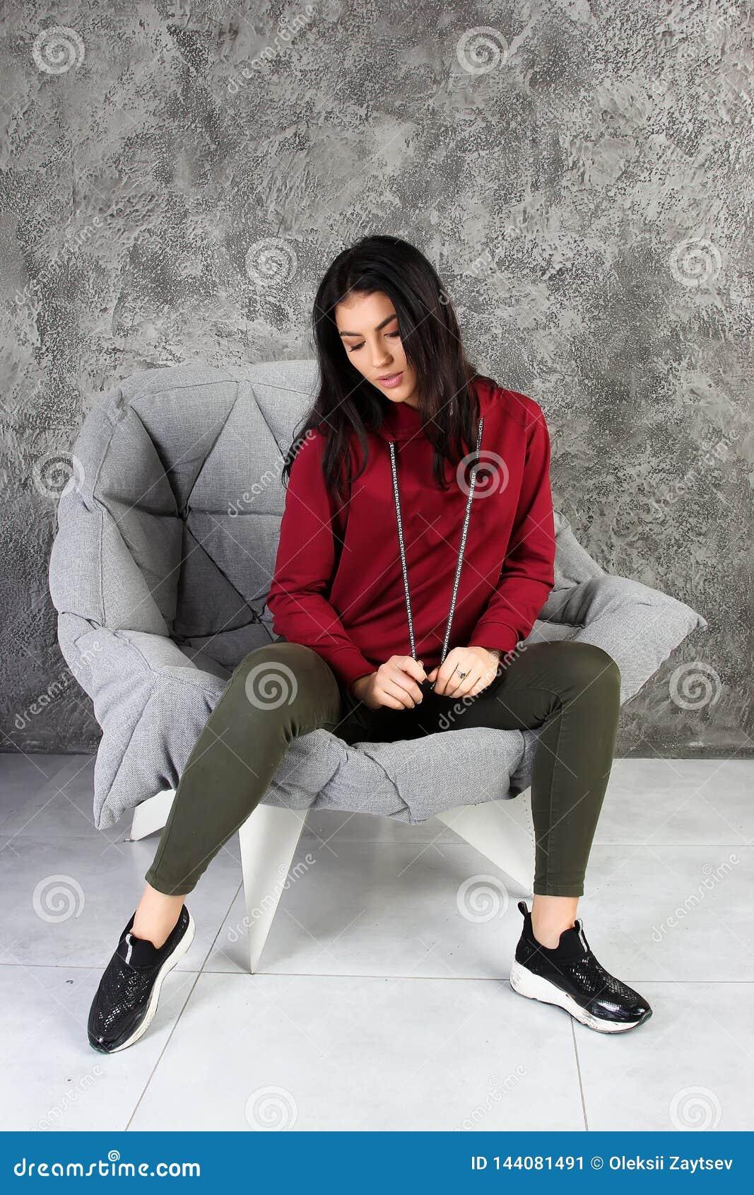 Młoda dziewczyna w tracksuit siedzi w eleganckim wnętrzu