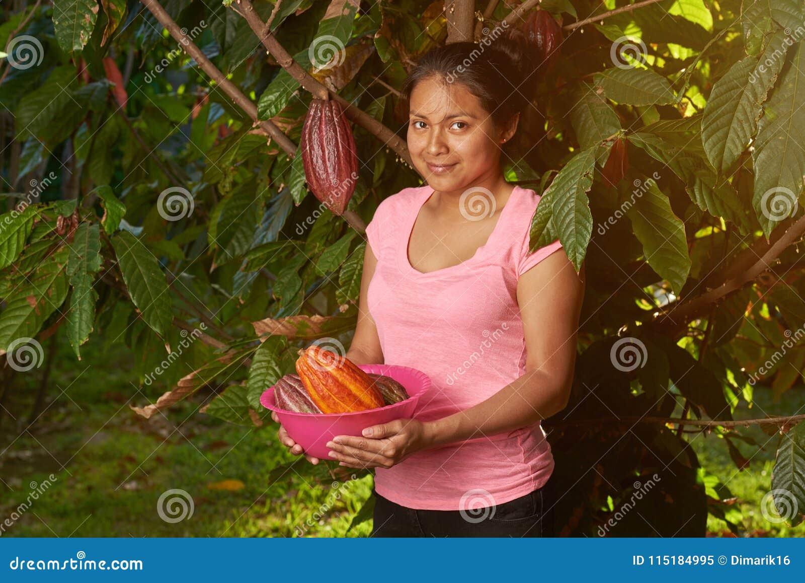 Młoda dziewczyna z świeżymi surowymi kakao strąkami
